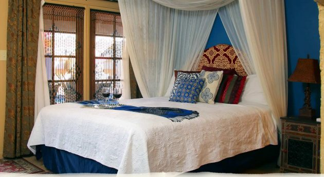 Deluxe King Room bed and windows with patio view