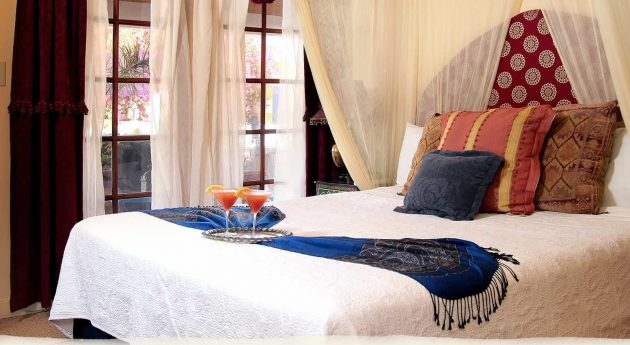 Standard King Room bed with drinks for guests and decorative pillows